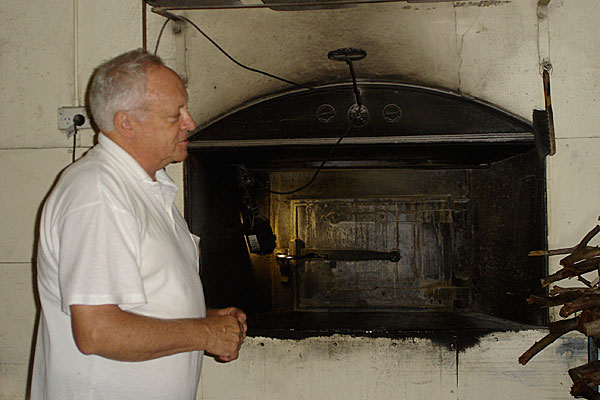 Brian (Nipper) Fechner proudly standing in front of his wood fired oven at the Apex Bakery